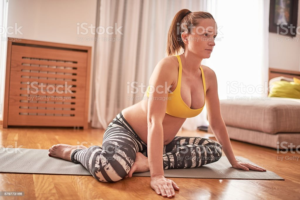 Pregnant woman exercising yoga stock photo