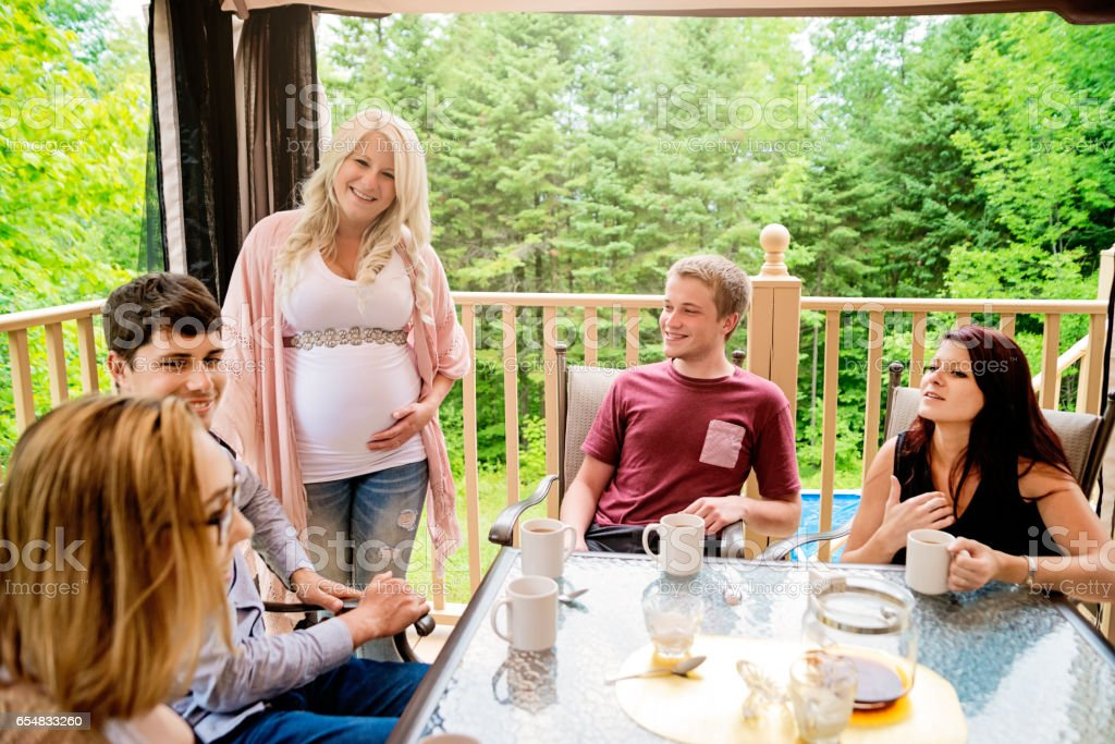 Pregnant woman having coffee with friends outdoors. stock photo