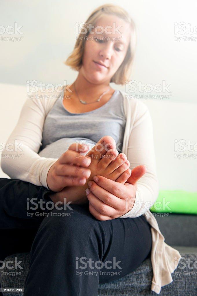 Pregnant woman having foot massage stock photo