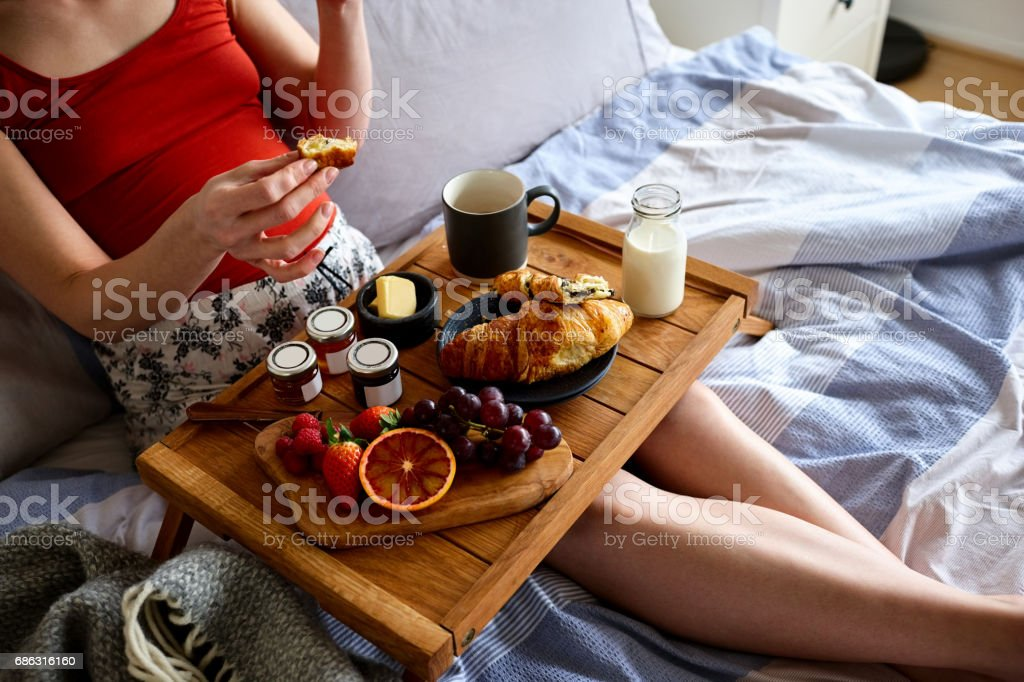Pregnant woman having healthy breakfast on bed stock photo