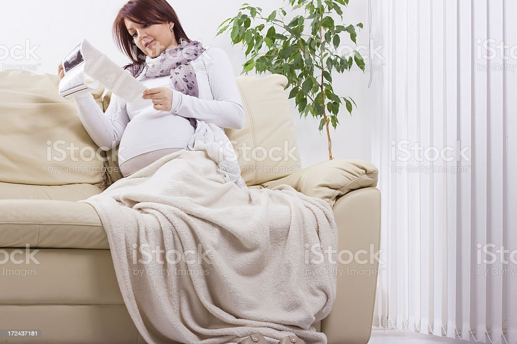 Pregnant woman holding a sonogram of her unborn child. royalty-free stock photo