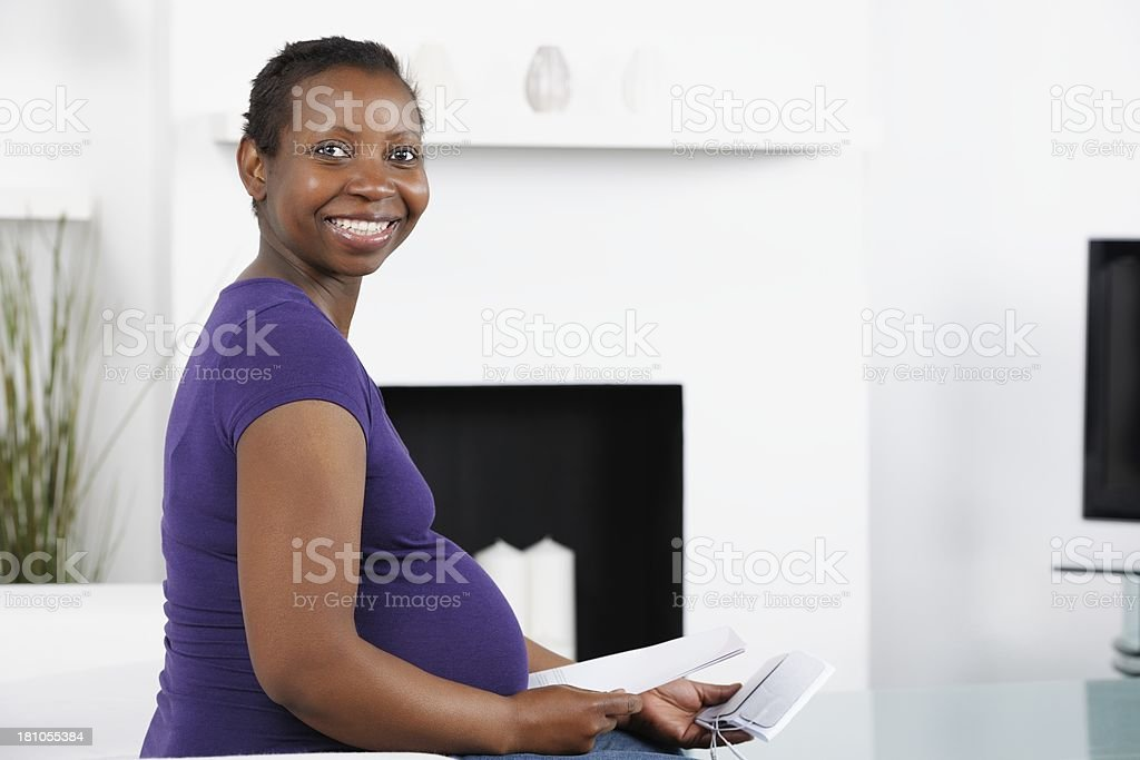 Pregnant  Woman Holding Instructions And Electrodes For TENS machine. royalty-free stock photo
