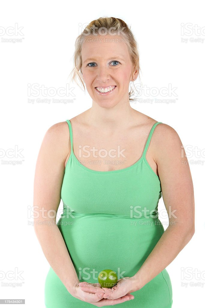 Pregnant woman holding lime (representing fetus size) royalty-free stock photo