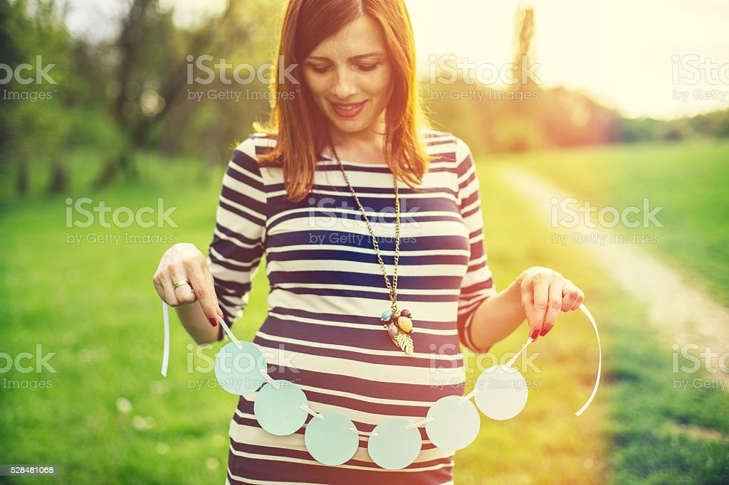 Pregnant woman holding name sign blanked out. stock photo