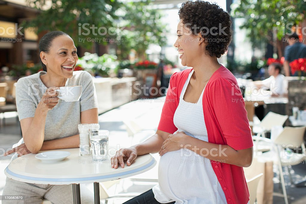 Pregnant woman holding stomach at cafe with friend royalty-free stock photo