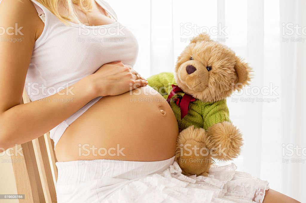 Pregnant woman holding teddy bear to her tummy stock photo