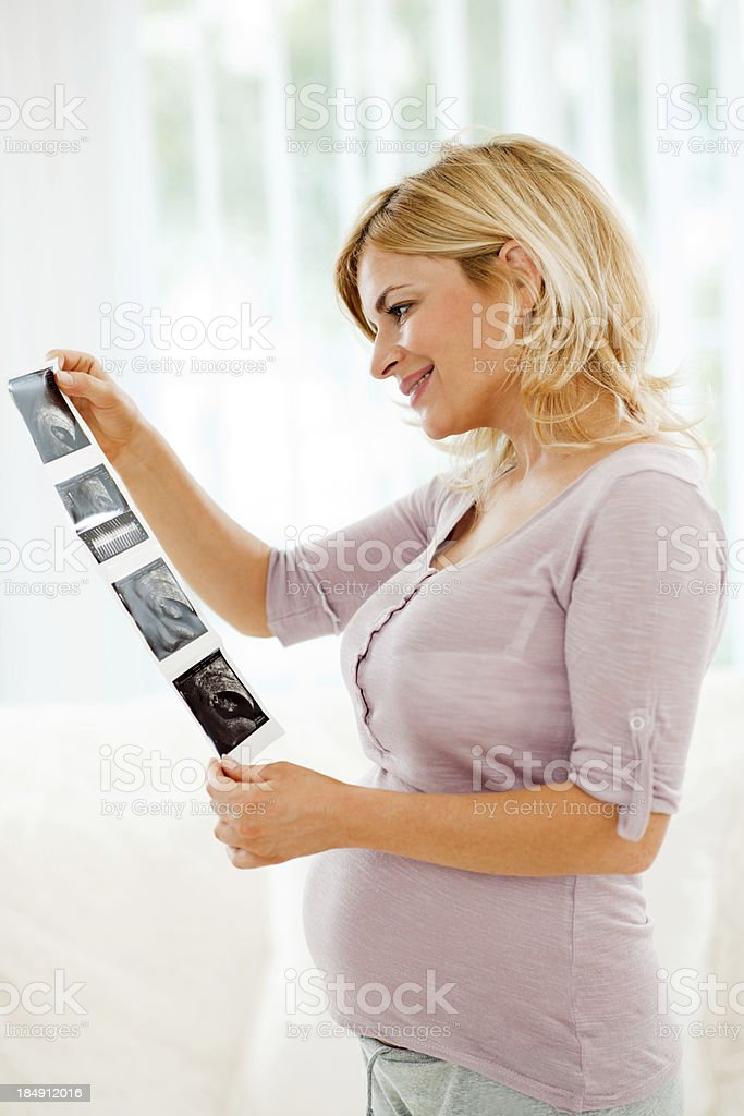 Pregnant woman holding ultrasound picture. royalty-free stock photo
