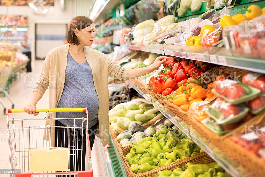 pregnant woman in a supermarket considering vegetables stock photo