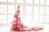 Pregnant woman in beautiful pink magnificent dress