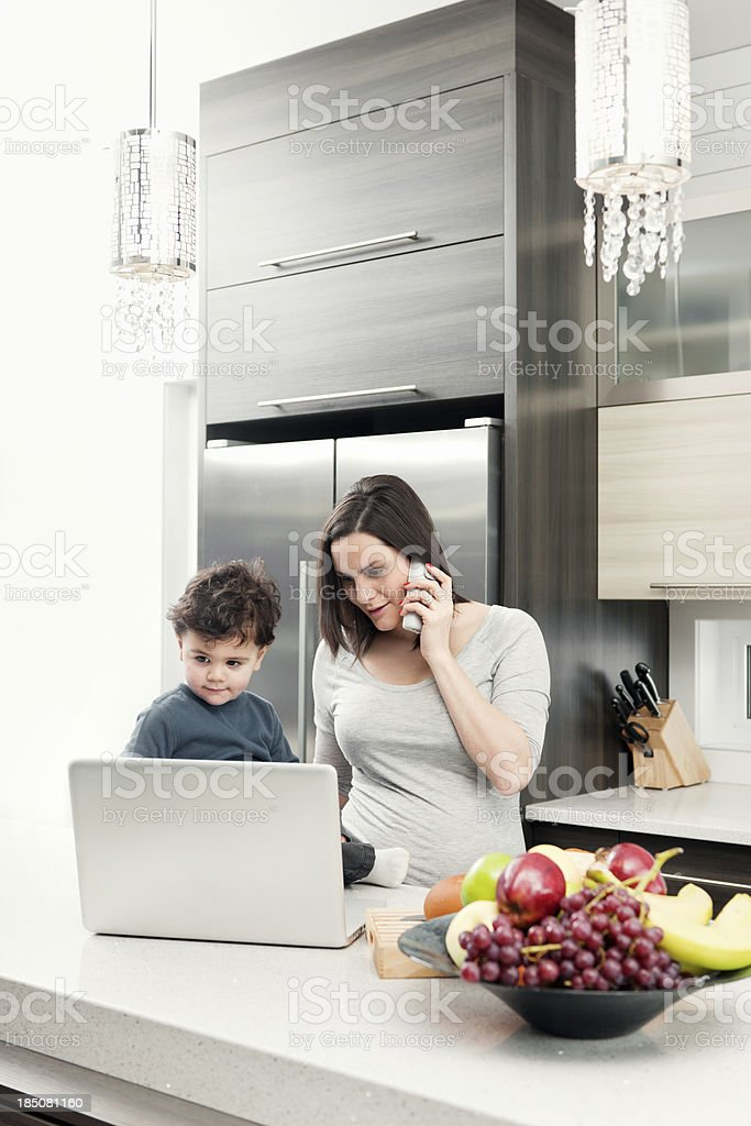 Pregnant woman in kitchen with son royalty-free stock photo