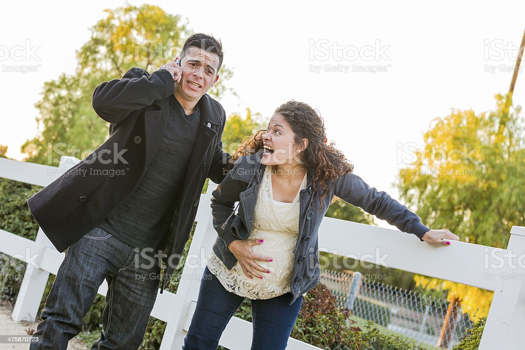 Pregnant Woman In Pain While Husband Uses Cell Phone Outside stock photo