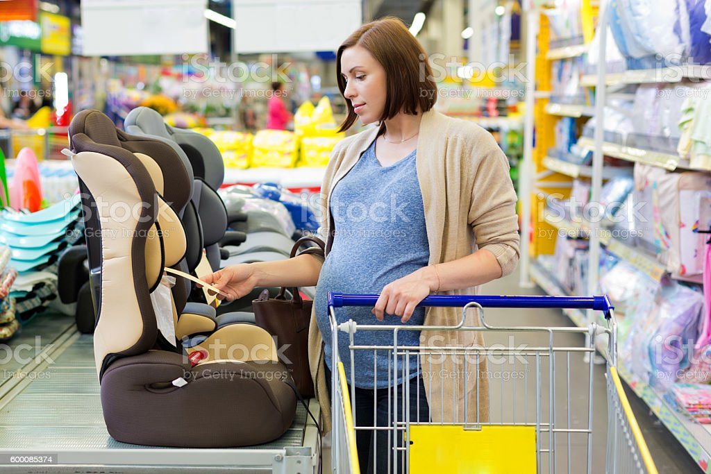 pregnant woman in shop buy car baby seat stock photo