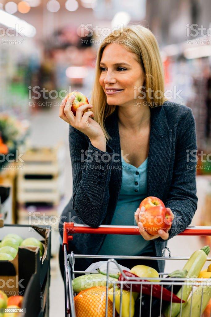 Pregnant Woman in Supermarket stock photo