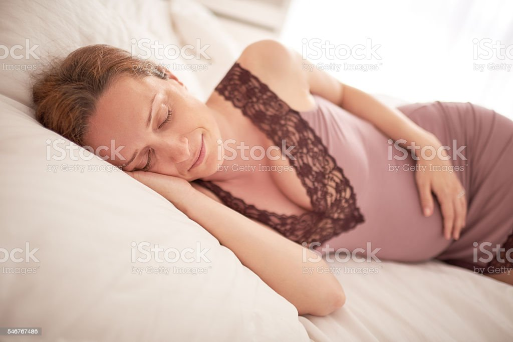 Pregnant woman in the bedroom stock photo