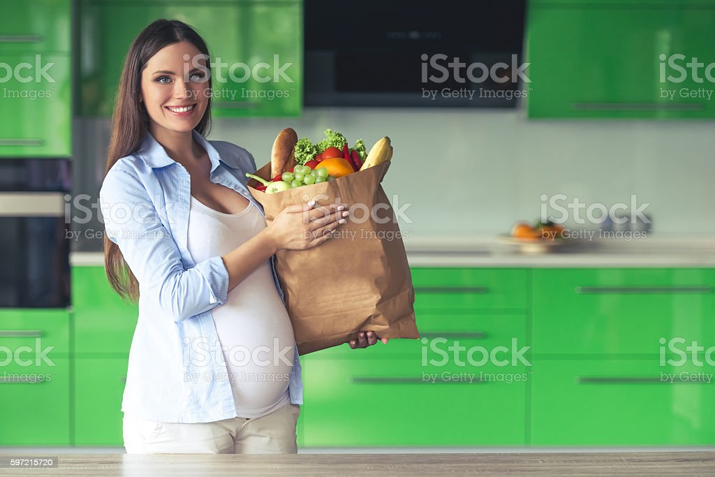 Pregnant woman in the kitchen stock photo