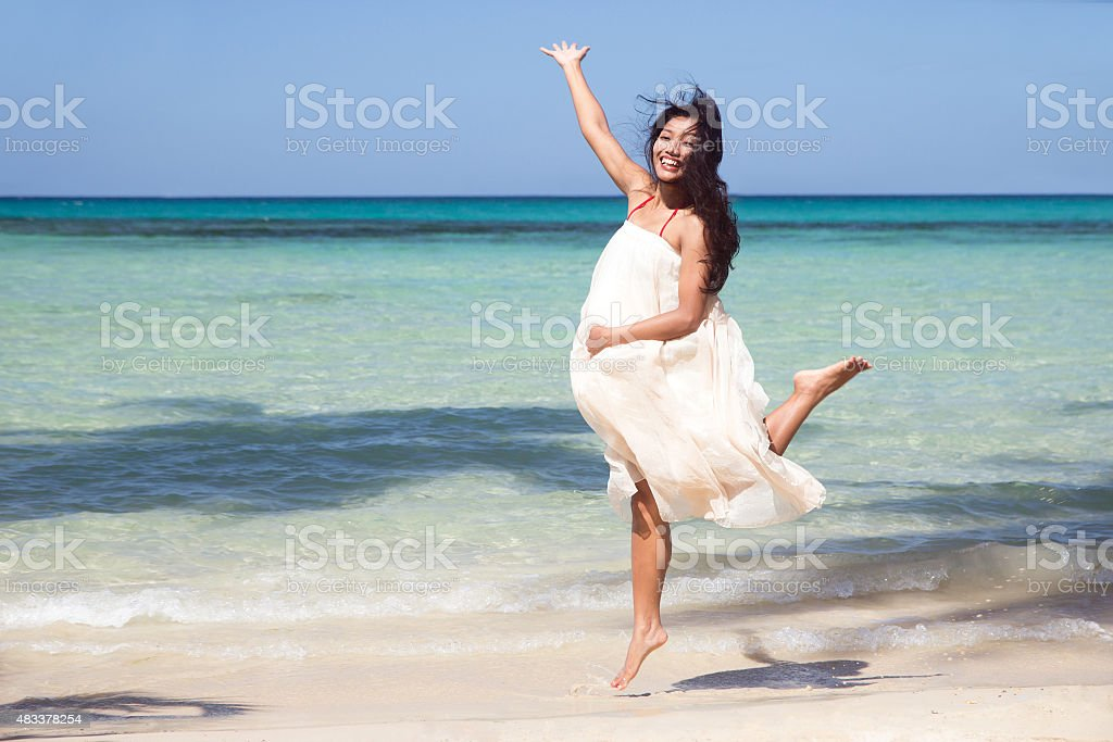 pregnant woman jumping on the beach stock photo