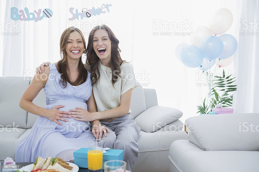 Pregnant woman laughing with her friend at baby shower stock photo