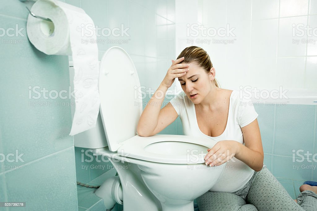 Pregnant woman leaning on toilet and feeling sick stock photo