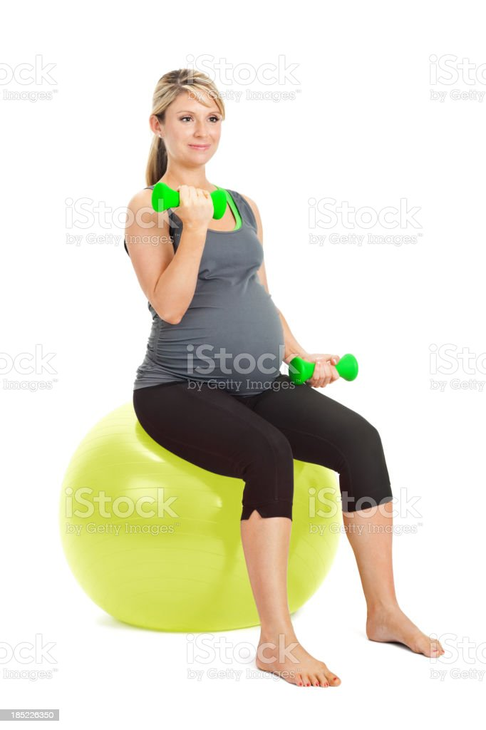 Pregnant woman lifting weights on exercise ball royalty-free stock photo