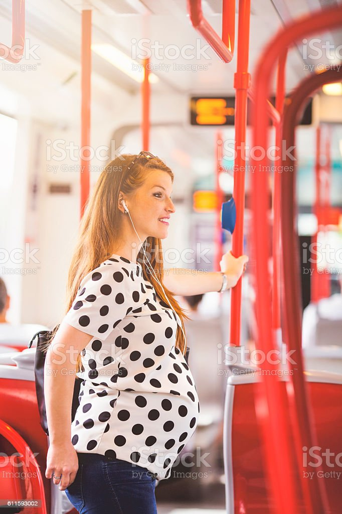 Pregnant woman listening music in street car stock photo