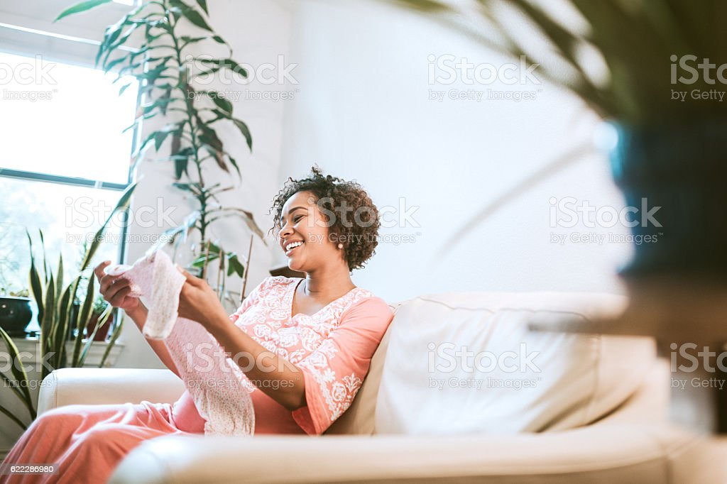 Pregnant Woman Looking At Baby Clothes stock photo