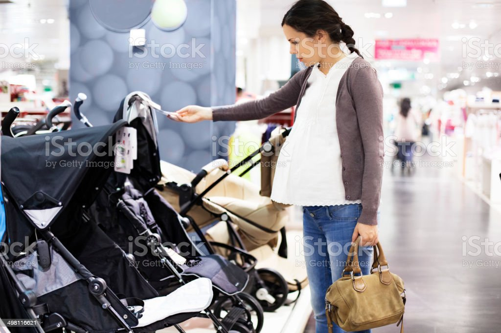 Pregnant woman looking at strollers stock photo
