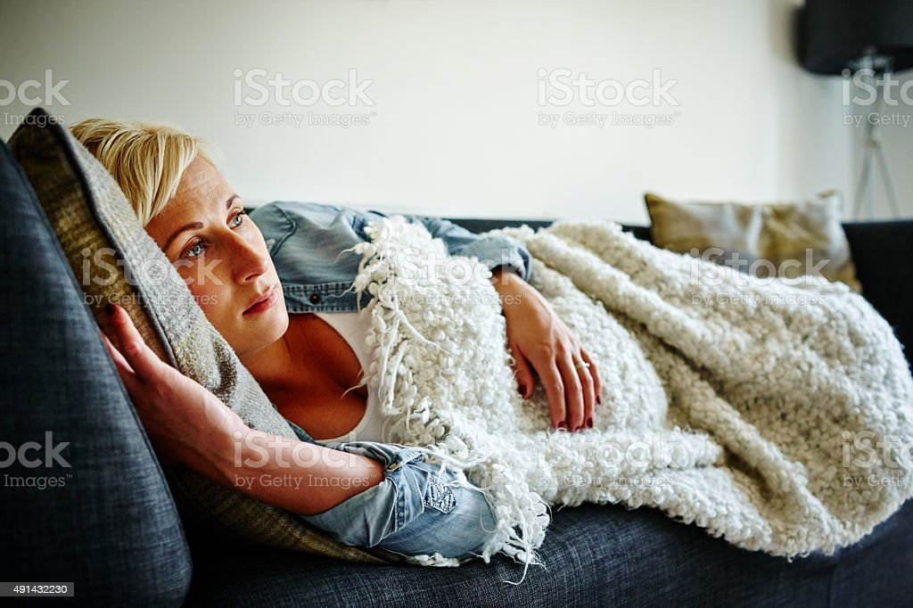 Pregnant woman lying on couch daydreaming stock photo