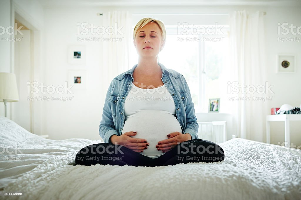 Pregnant woman meditating on bed stock photo