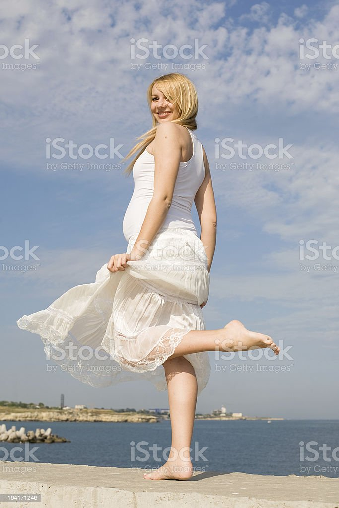 Pregnant woman on seashore royalty-free stock photo