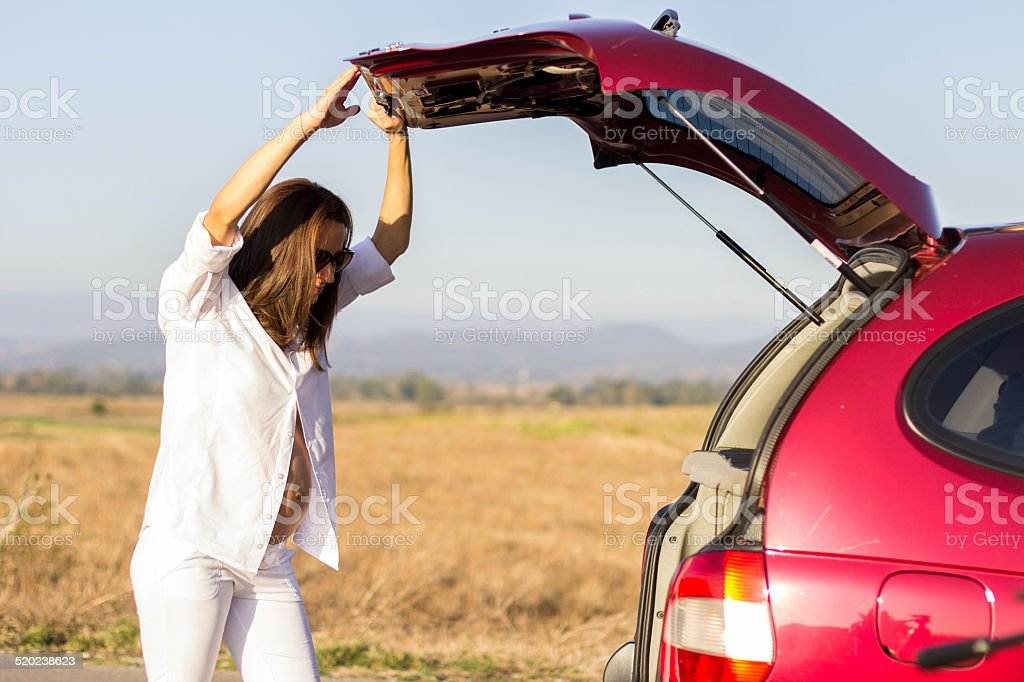 Pregnant woman opening car trunk stock photo
