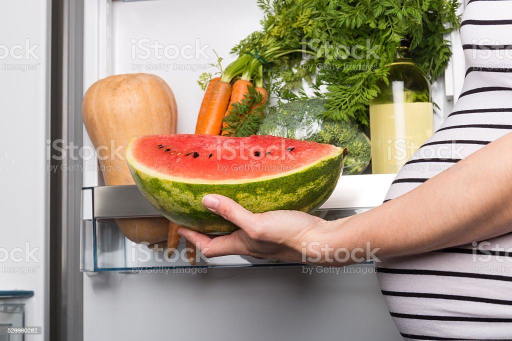 Pregnant woman opening fridge witch vegetables stock photo