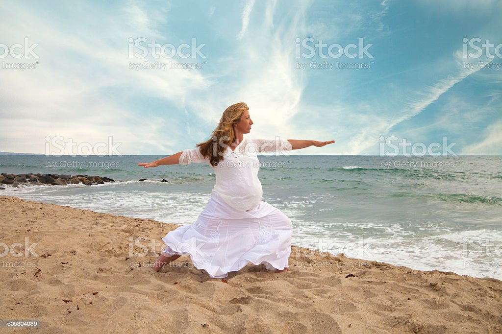 Pregnant woman practicing yoga at the beach stock photo