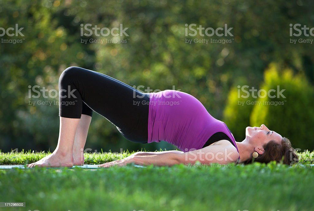 Pregnant Woman Practicing Yoga Bridge Pose Outdoors. stock photo