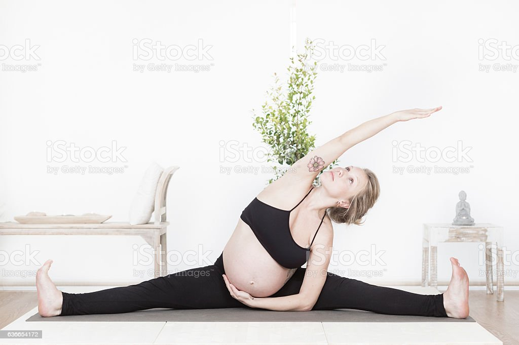 Pregnant woman practicing yoga stock photo