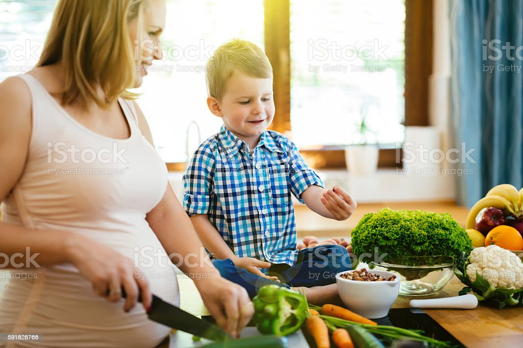 Pregnant woman preparing meal with son stock photo