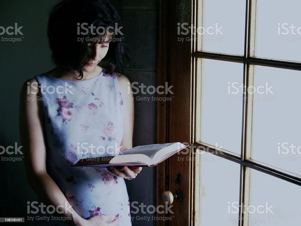 Pregnant Woman Reading, Low Key stock photo