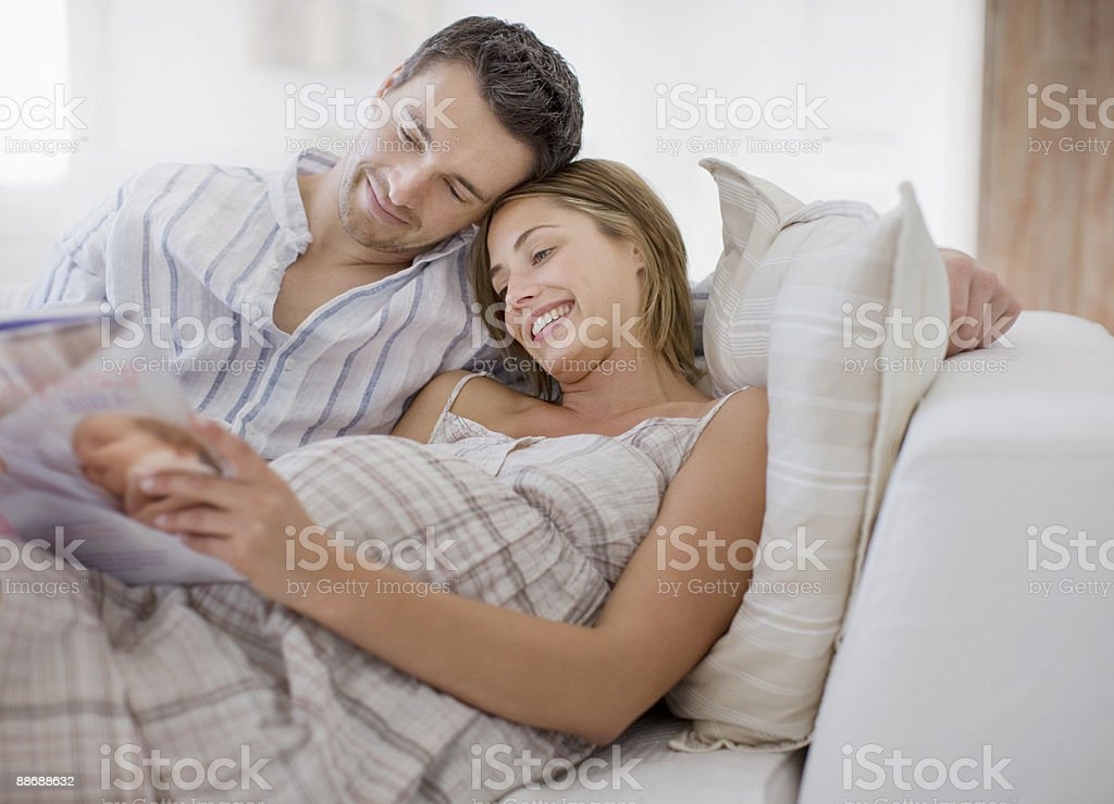 Pregnant woman reading magazine with husband royalty-free stock photo