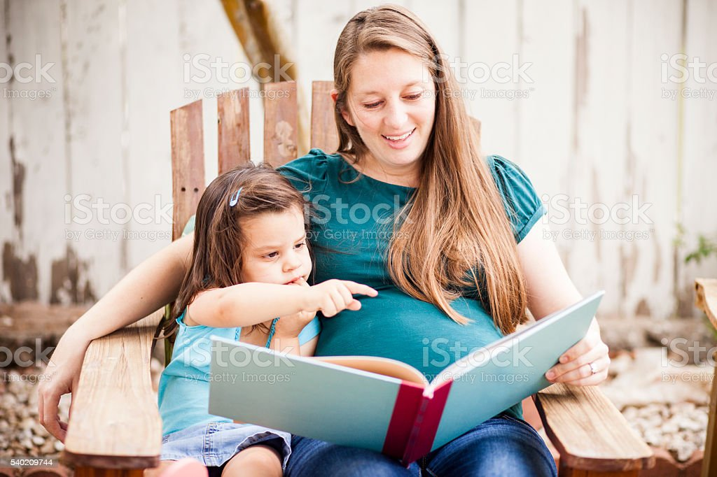 Pregnant Woman Reading to Daugther in Backyard stock photo