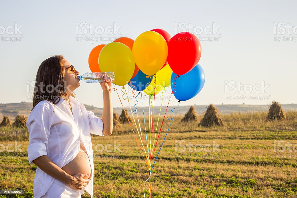 Pregnant woman refreshing herself stock photo