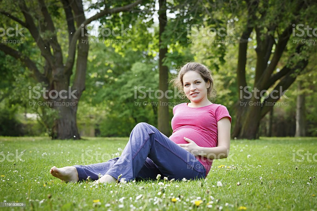 Pregnant woman relaxing in the park stock photo