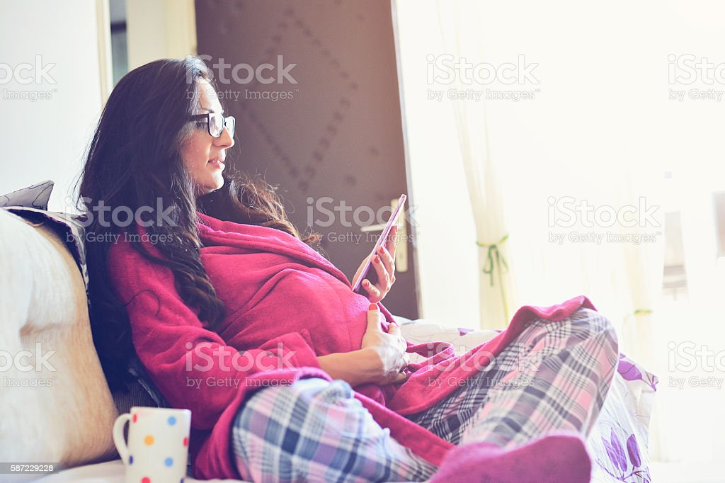 Pregnant woman relaxing with her tablet drinking tea stock photo