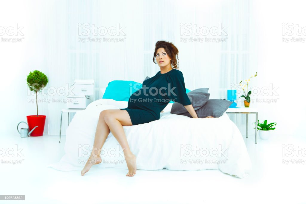 Pregnant woman resting on bed royalty-free stock photo