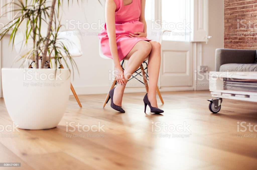 Pregnant woman rubbing foot stock photo