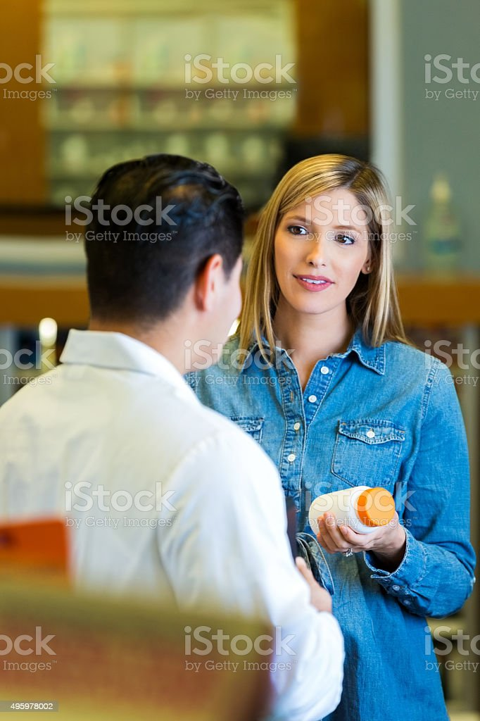 Pregnant woman shopping for prenatal vitamins in pharmacy stock photo