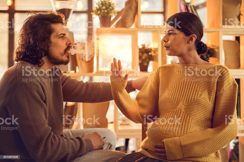 Pregnant woman showing stop smoking gesture to her boyfriend. stock photo