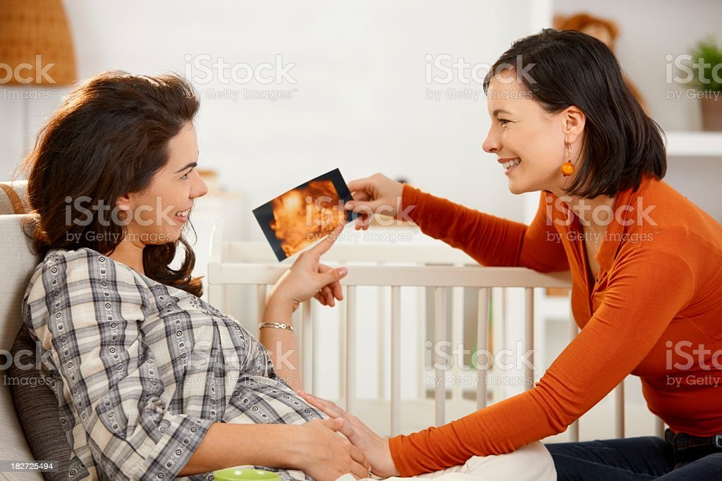 Pregnant woman showing ultrasound image to friend royalty-free stock photo