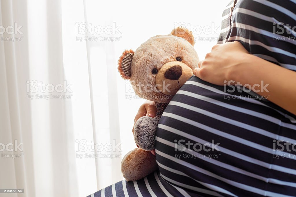 Pregnant woman sitting and holding teddy bear toy stock photo