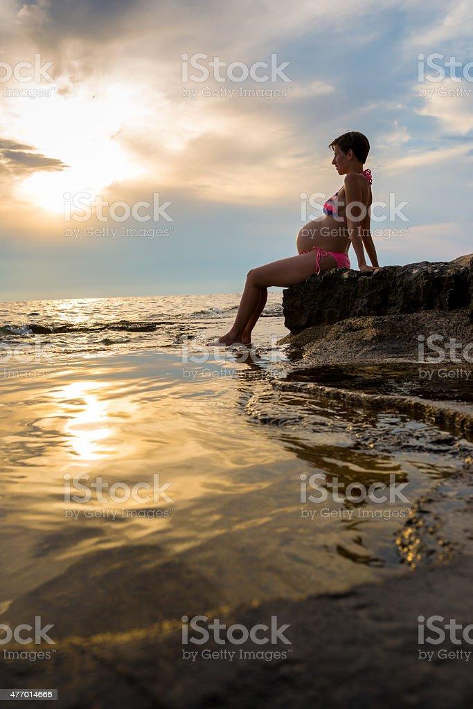 Pregnant Woman Sitting at Shore stock photo
