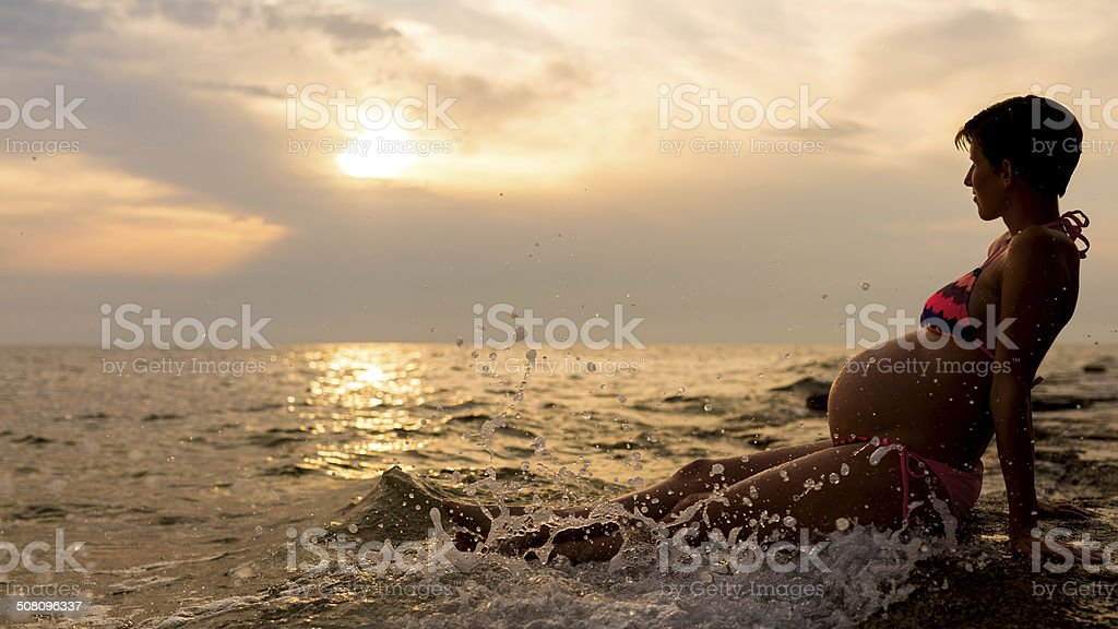 Pregnant woman sitting in the shallow water stock photo