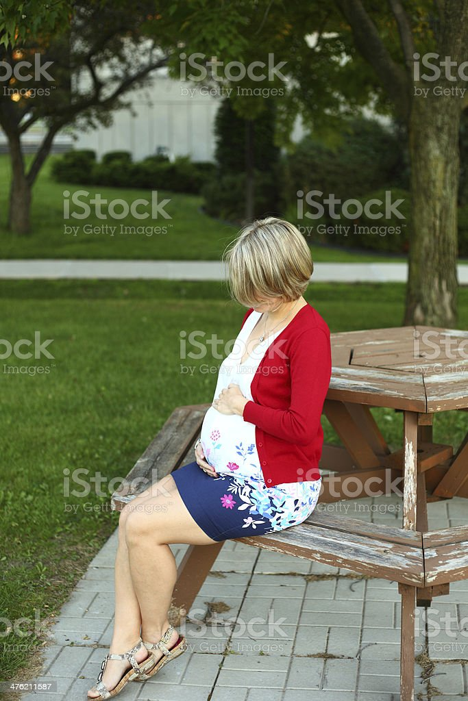 Pregnant woman sitting on a bench looking at her belly stock photo